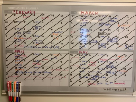 Photo of the 4-month calendar—February through May—on the wall of my office. All the dates are crossed out. You can make out all daily events.