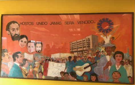"Mural featuring Hostos' main building in the background, surrounded by people apparently celebrating, playing music, and holding protest signs. The head of Eugenio María de Hostos floats in the sky. Text at top says ""Hostos Unido Jamas Sera Vencido."""